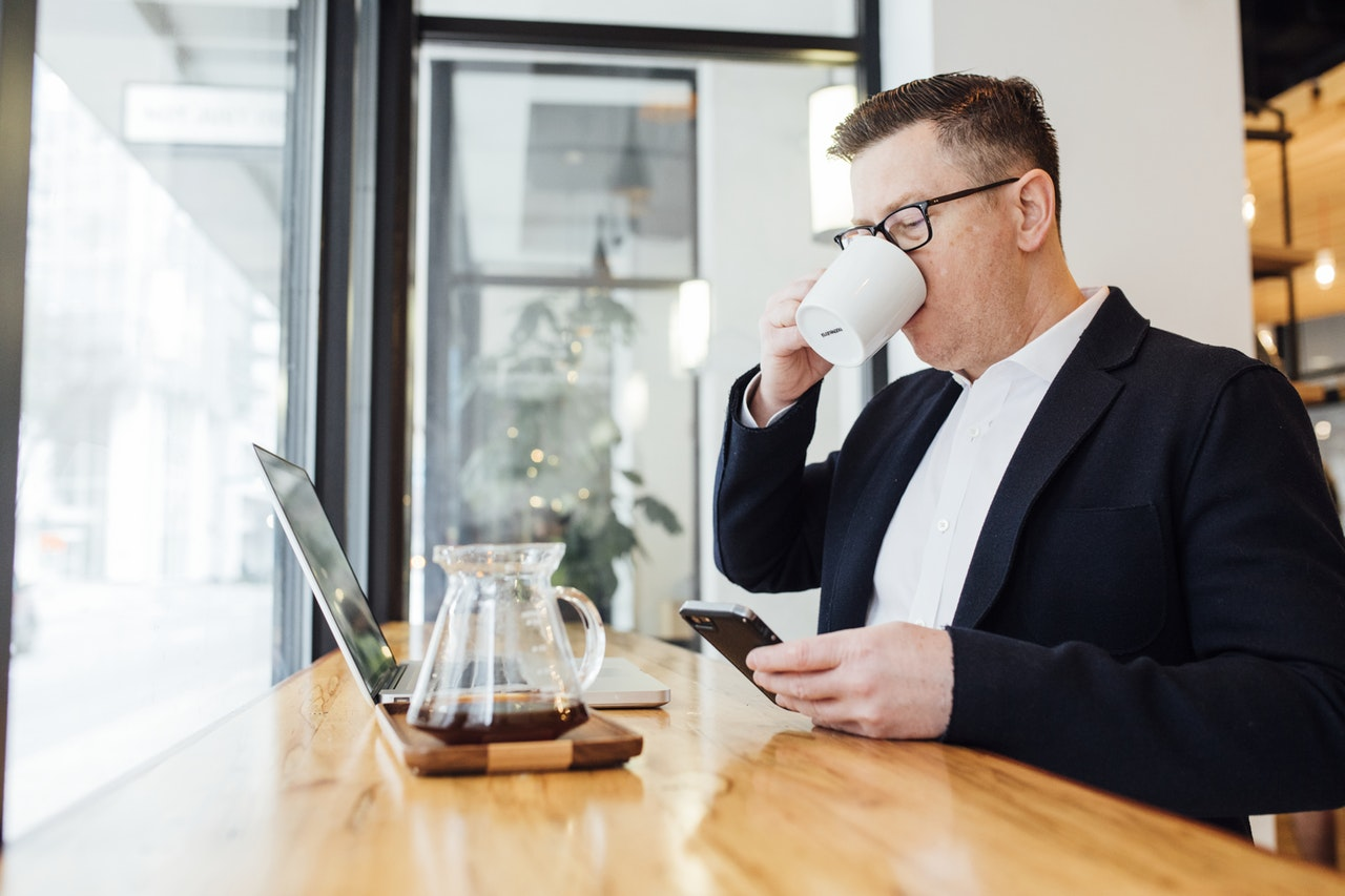 man drinking coffee in front of laptop