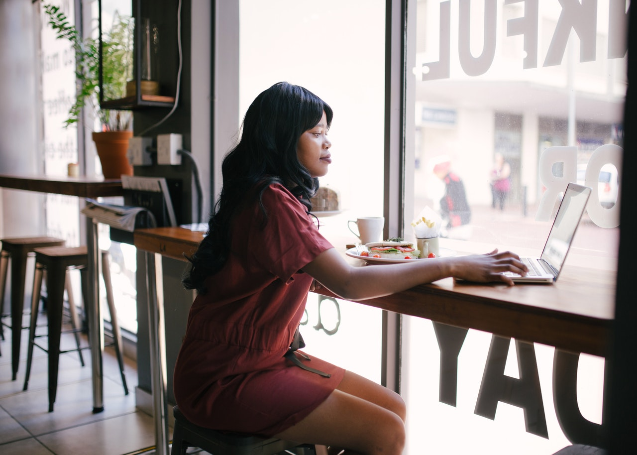 woman in red dress working remotely
